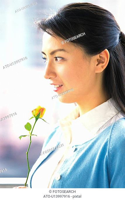 Image of a Mid Adult Woman Holding an Orange Rose, Looking Sideways, Smiling, Side View