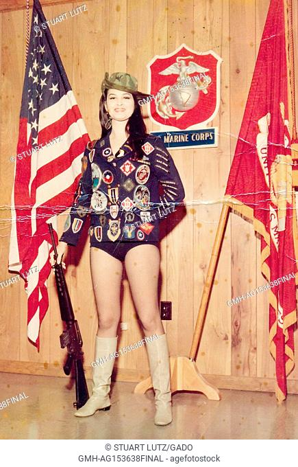 A young, female American USO performer wearing suggestive clothing and a cowboy hat and boots, with a jacket which has many colorful patches