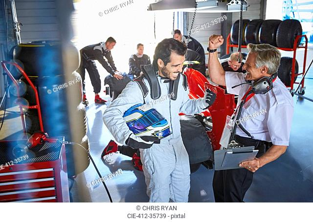 Driver and formula one race car driver cheering, celebrating victory in repair garage