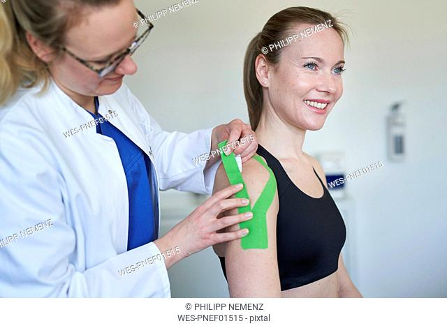 Female doctor applying tape to shoulder of patient in medical practice