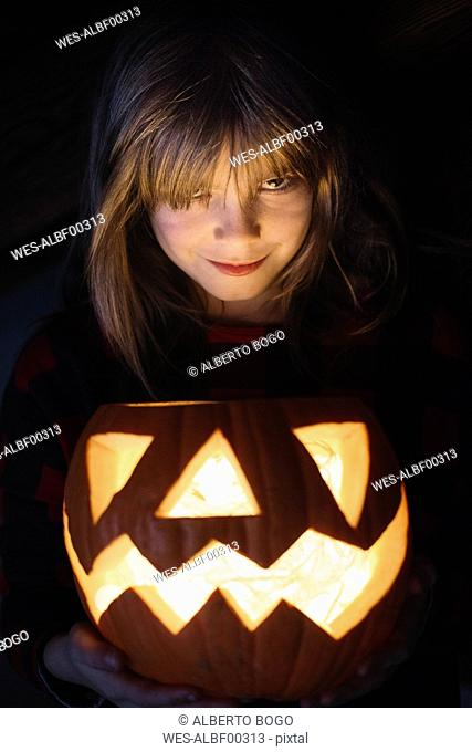 Portrait of smiling girl with lighted Jack O'Lantern at Halloween
