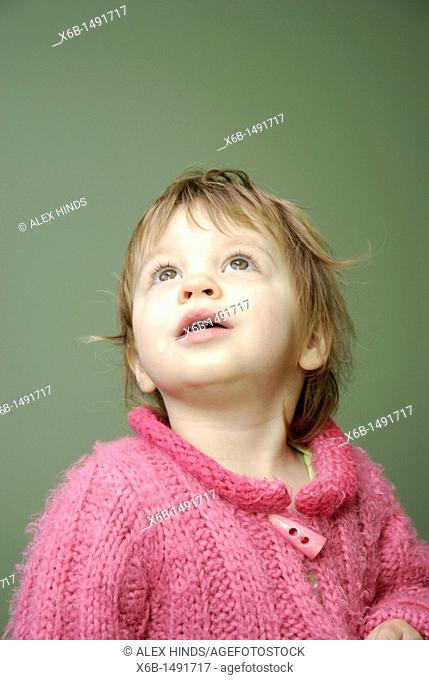 A twenty month old girl looking up with an expression of interest