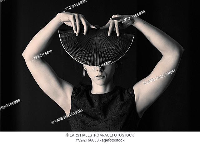 Hispanic woman covering her face with foldable hand fan