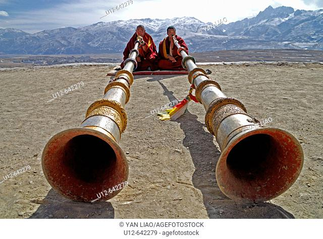 two monks playing the long tibetan Ragdun - horn on the roof of the Garze monastery , Sichuan, China
