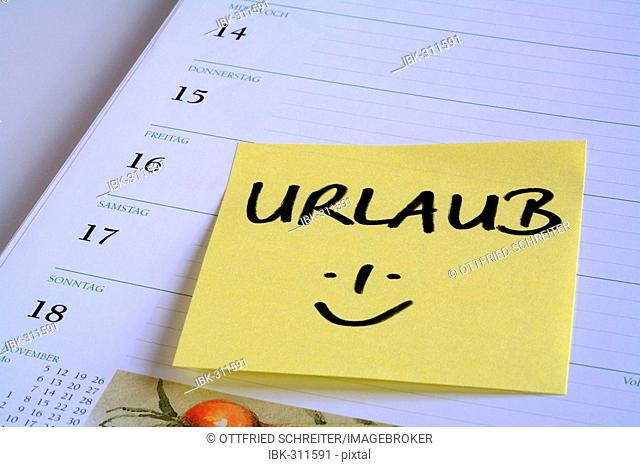 Yellow reminder note Urlaub (holiday) on the page of a calendar