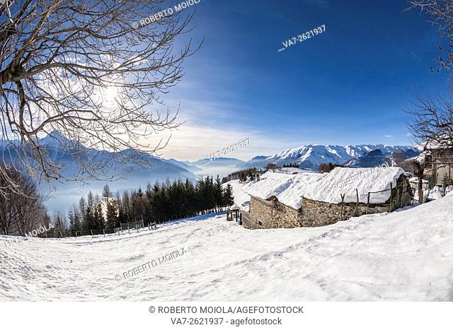 Winter view of Lake Como and mountain hut Vercana mountains High Lario Lombardy Italy Europe