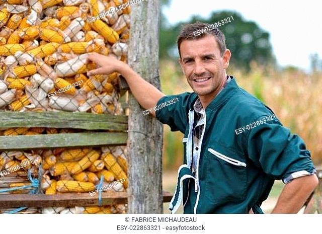 Cheerful farmer standing by corn silo