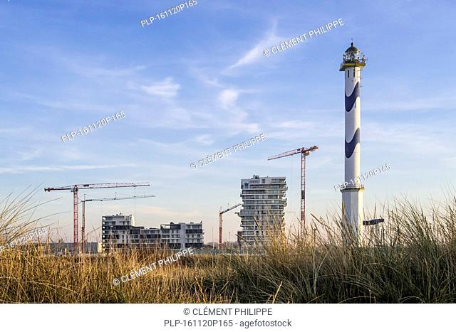 Lighthouse Lange Nelle and new flats being build for real estate project Oosteroever in the Ostend harbour along the Belgian North Sea coast, Belgium