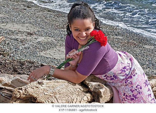 This pretty multi-racial woman in her thirties is smiling and happy on the beach She is holding some red carnations and laying on her stomach on some driftwood...