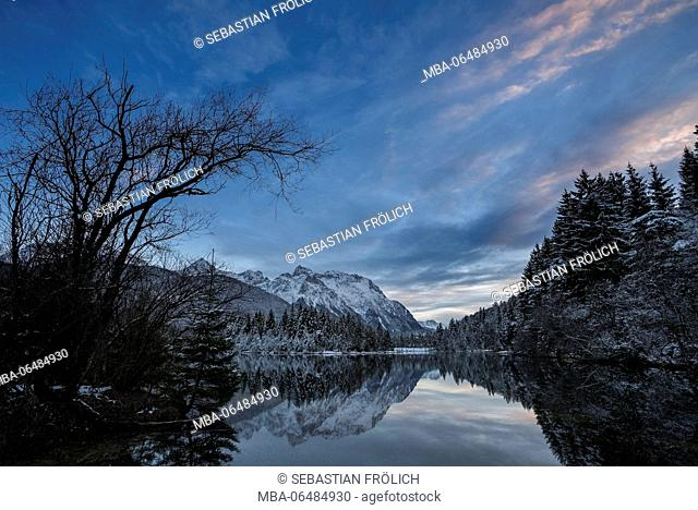 The reservoir Krün in the last evening light. In the background the snow-covered western Karwendelgebirge (mountains) with mirroring in the water