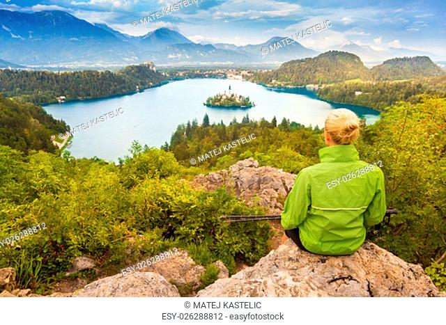 Young spoty active lady with hiking sticks admires beautiful nature around Bled Lake in Julian Alps, Slovenia