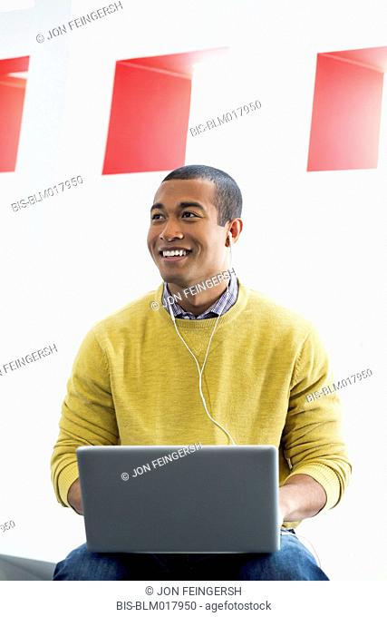 Mixed race man using laptop and earphones