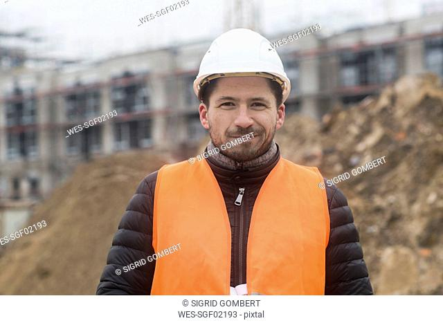Portrait of content man wearing safety vest and helmet at construction site