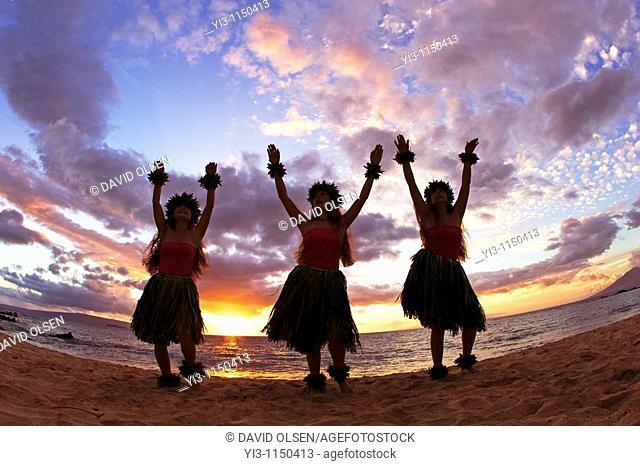 Three hula dancers at sunset at Palauea Beach, Maui, Hawaii, USA