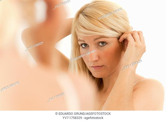 Beautiful young blonde preening in the mirror