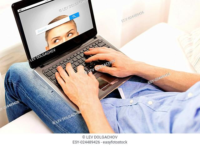 technology, internet, information, people and lifestyle concept - close up of male hands typing on laptop computer with search browser bar on screen at home