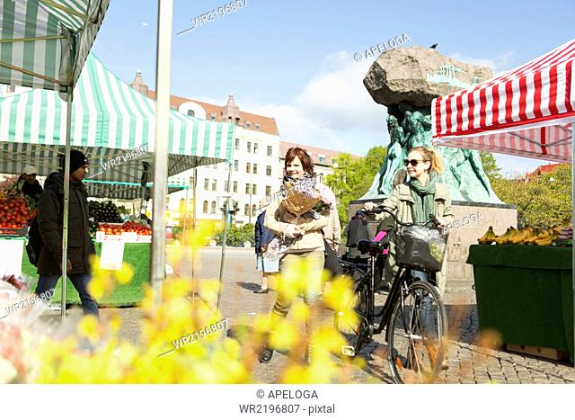 Mature women with bicycle walking in market