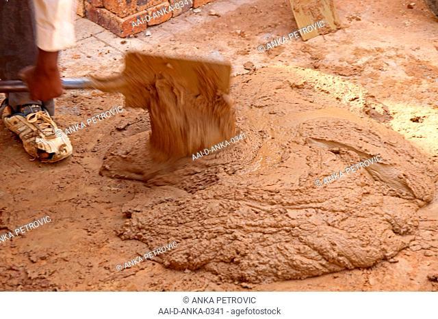 Worker shoveling cement concrete mixture, construction site, Moreleta Park, Pretoria, Gauteng Province, South Africa