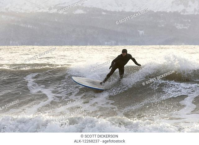 Person surfing in winter in Homer, Kenai Peninsula, Kachemak Bay, Alaska