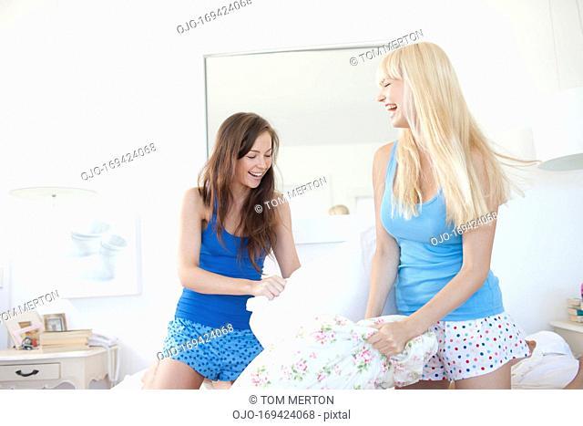 Women pillow fighting in bedroom