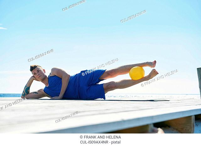 Man on pier lying on side resting on elbow, ball between legs