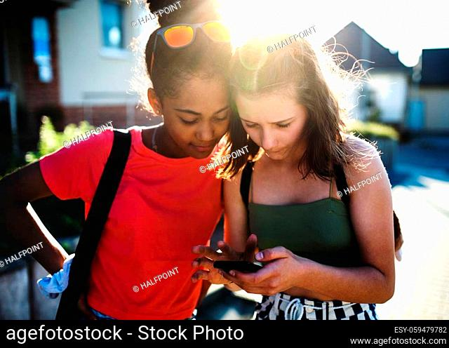 Front view of teenager girls friends outdoors in city, using sartphone