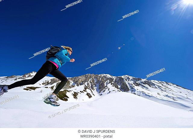 Jogger running through snowy mountains
