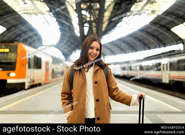 Portrait of smiling young woman at the train station