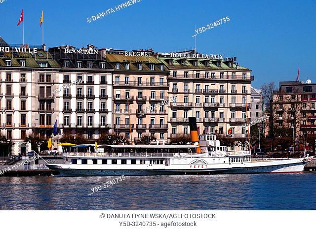 Facades of luxury hotels, Quai du Mont -Blanc along Lake Geneva seen from Mont-Blanc bridge, in front one of historic cruise steamboat name Vevey, Geneva