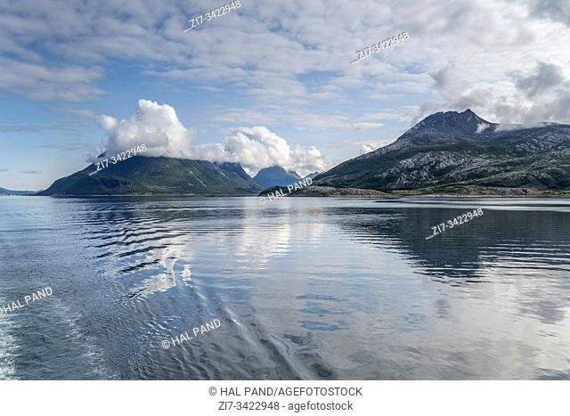landscape with cloud capped steep hills reflecting in fjord calm waters, shot under bright summer light at Stigfjord, Norway