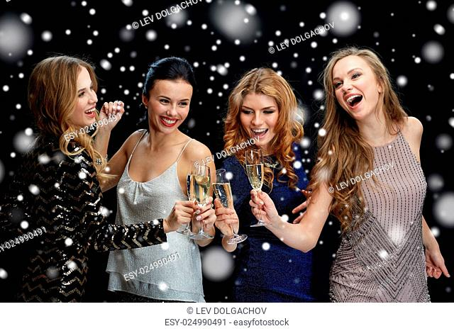 new year party, christmas, winter holidays and people concept - happy women clinking champagne glasses and dancing over black background with snow