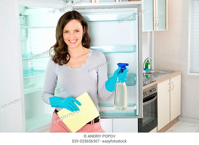 Young Beautiful Woman Standing With Rag And Spray Bottle Near The Open Fridge