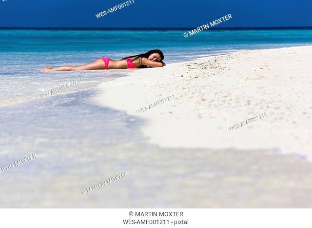Maldives, Young woman in bikini lying in shallow water