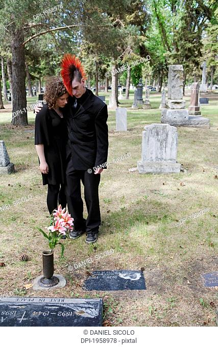 A Young Man And Young Woman Put Flowers By A Tombstone; Edmonton, Alberta, Canada