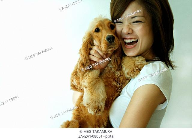 Young woman carrying a dog and laughing
