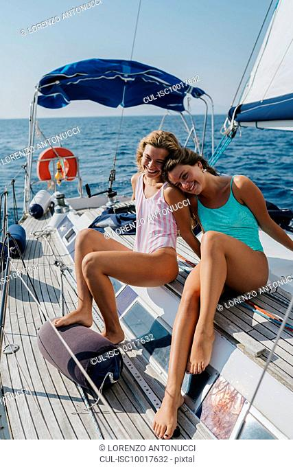 Friends relaxing on deck of sailboat, Italy