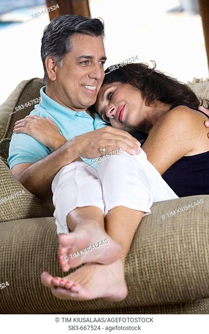 Woman sitting on mans lap on the living room couch