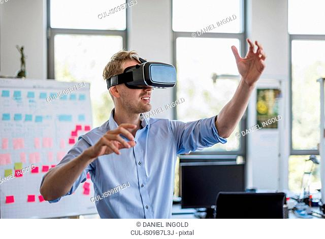 Mid adult businessman wearing virtual reality headset doing office presentation