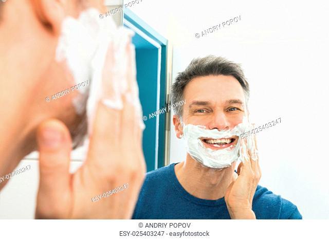 Close-up Of Happy Man Looking In Mirror Applying Shaving Cream