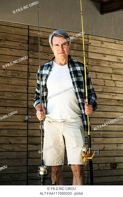 Mature man holding fishing rods