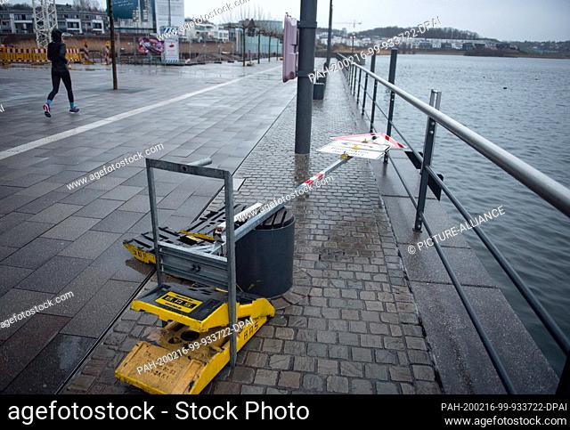 16 February 2020, North Rhine-Westphalia, Dortmund: A jogger is running near an overturned sign on the promenade of Lake Phoenix