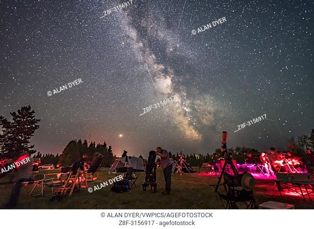 An observer gazes skyward with his Dobsonian reflector telescope at the Saskatchewan Summer Star Party on August 9, 2018