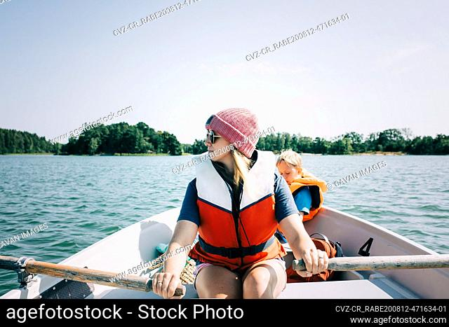 woman rowing a boat with her kids in Sweden in the summer