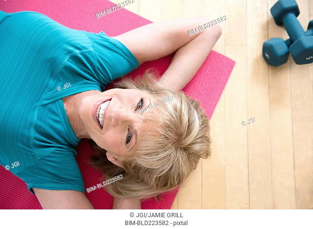 Older Caucasian woman relaxing on exercise mat