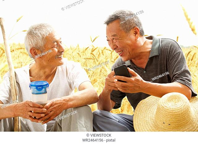 Two farmers sitting in field talking