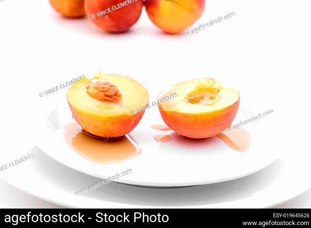 fresh peaches with syrup on a white plate