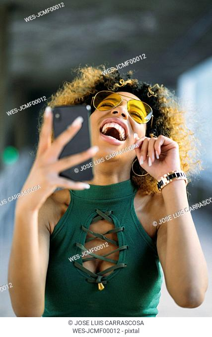 Portrait of laughing young woman with smartphone outdoors