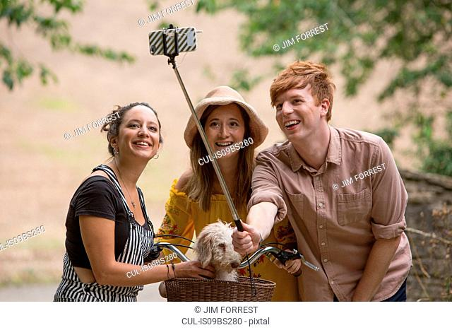 Friends taking selfie with pet dog in countryside