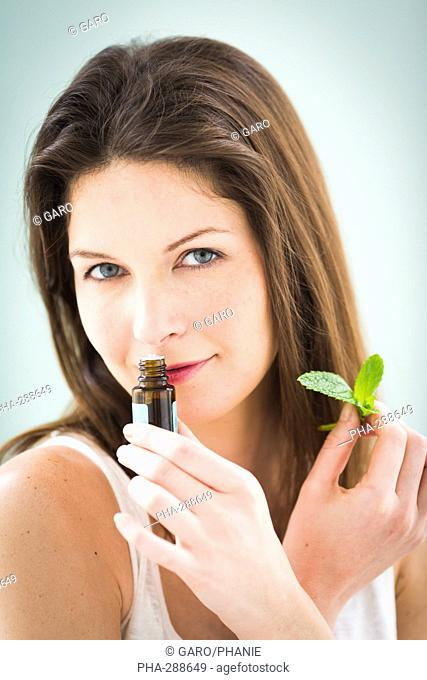 Woman smelling a bottle of mint essential oil