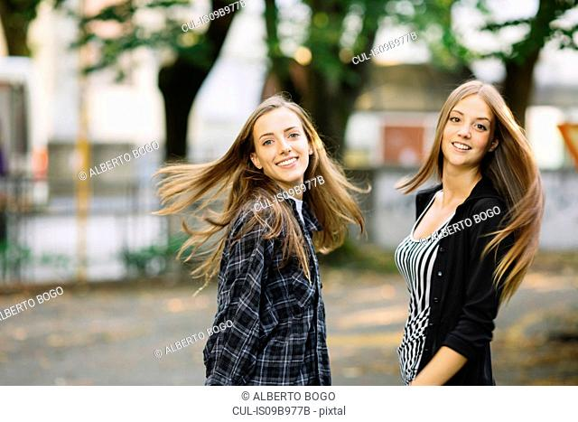 Portrait of two young female friends swirling long brown hair in park